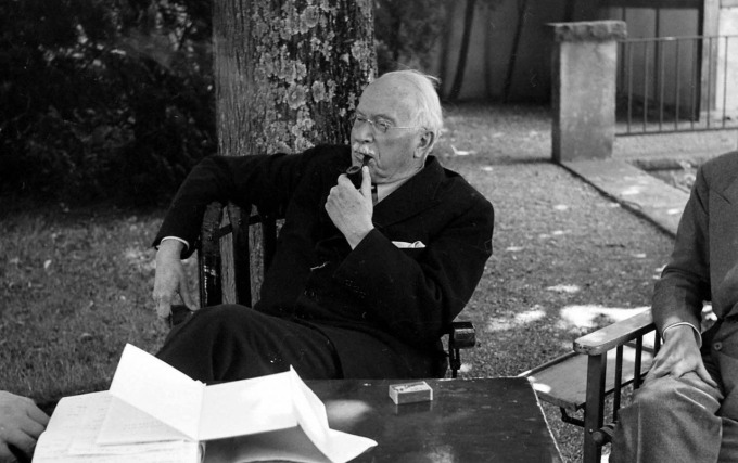 JFKCurious Carl Jung in his house's garden sitting and smoking pipe in Knusnacht, Switzerland, 1949 (1)